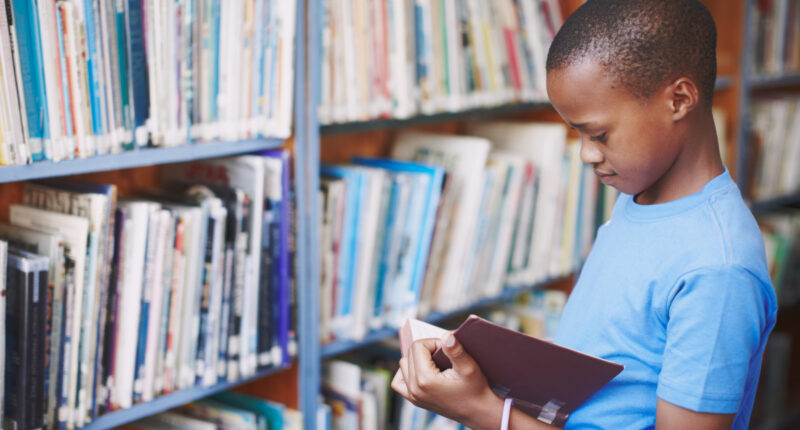Young Black boy reading in library