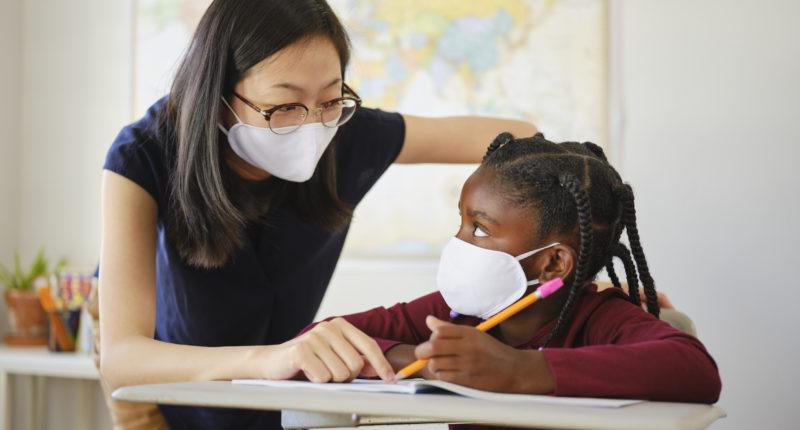 Teacher helping a young Black girl with an an assignment